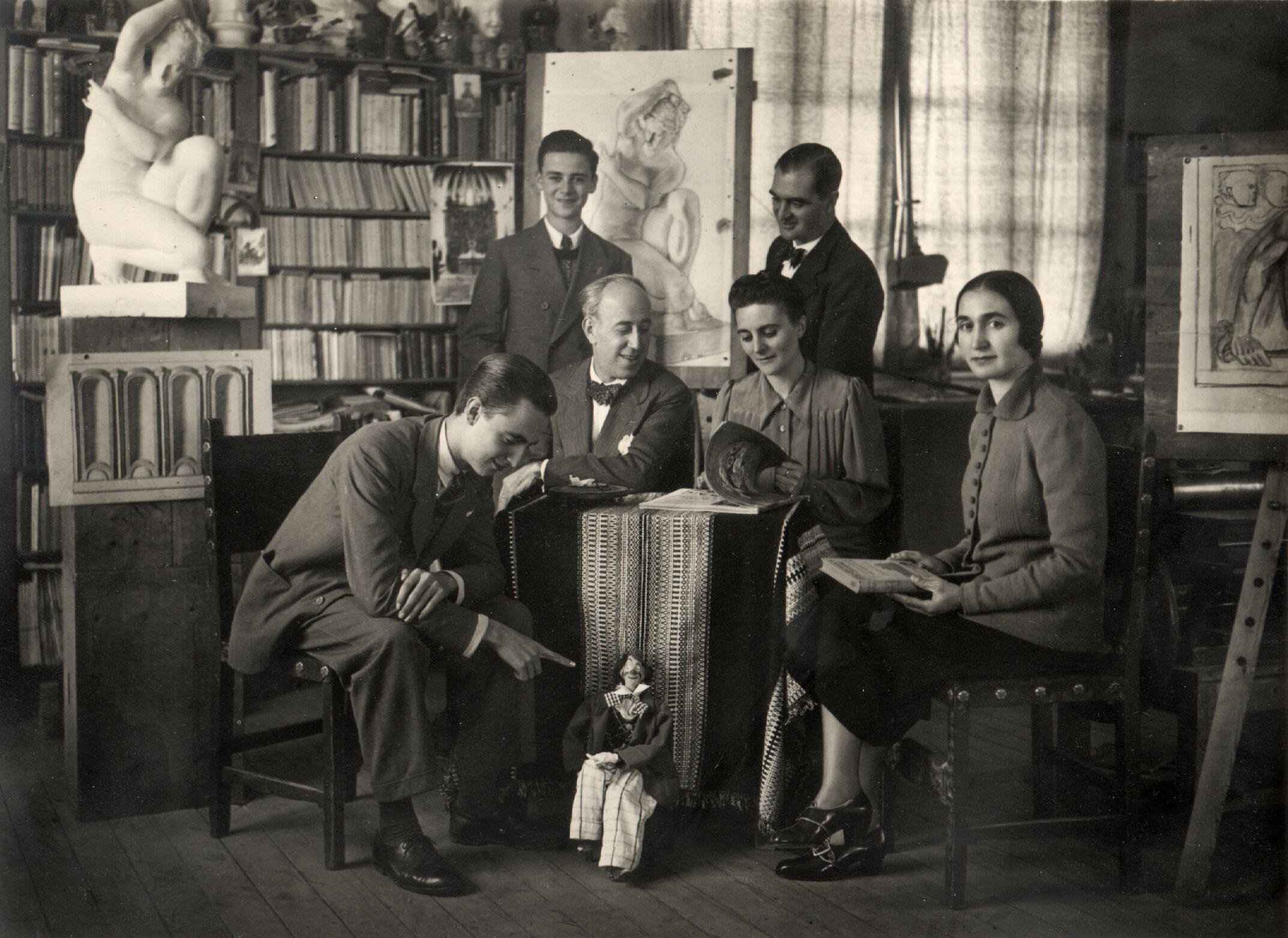 Fotografía de la familia Lanz, en Granada, años 19040. Totolín aparece junto a la mesa. En el centro de la imagen están sentados Hermenegildo Lanz y su esposa Sofía Durán. Su hijo Gildo aparece sentado en primer plano a la izquierda, y señala a la marioneta. El otro hijo de la familia, Enrique Lanz, está de pie, sonriente, detrás de su padre.